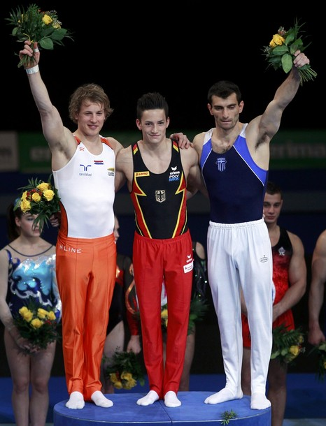 Winners pose during flower ceremony after parallel bars competition at men's apparatus finals during Artistic Gymnastics European Championships in Berlin
