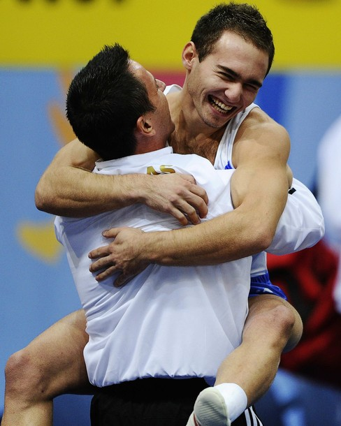 Eleftherios Kosmidis of Greece (R) celebrates his victory with his coach after his performance during the men's floor finals at the Artistic Gymnastics World Championships in Rotterdam October 23, 2010. REUTERS/Dylan Martinez (NETHERLANDS - Tags: SPORT GYMNASTICS IMAGES OF THE DAY)