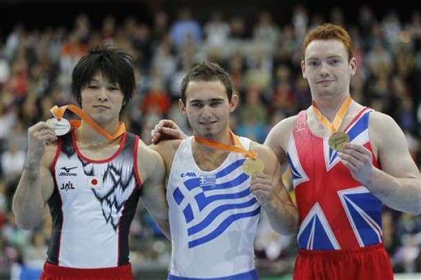 Kohei Uchimura of Japan, left, silver medal, Elefterios Kosmidis of Greece, center, gold medal, and Daniel Purvis of Britain, right, bronze medal, celebrate on the podium of the World Championships Gymnastics in Rotterdam, Netherlands, Saturday Oct. 23, 2010. (AP Photo/Bas Czerwinski)