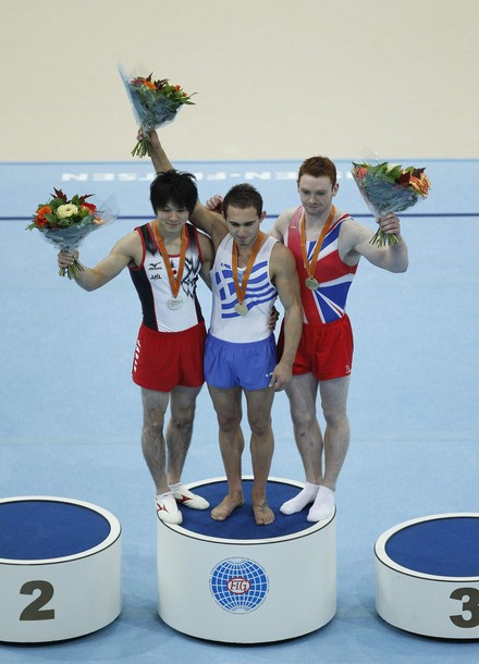 Kohei Uchimura of Japan (L), Eleftherios Kosmidis of Greece and Daniel Purvis of Britain(R) celebtrate on the podium after the men's floor finals at the Artistic Gymnastics World Championships in Rotterdam October 23, 2010. REUTERS/Jerry Lampen (NETHERLANDS - Tags: SPORT GYMNASTICS)